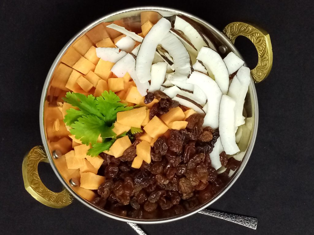 shredded fresh coconut, raisins and cut in cubes raw sweet potatoes in a nice metal bowl with golden handles
