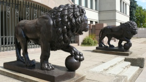 Sculptures of two lions in front of the building. One of the front paws of both lions is placed on a ball