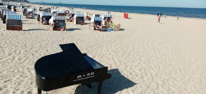 black grand piano standing on a beach close to the sea and windshields