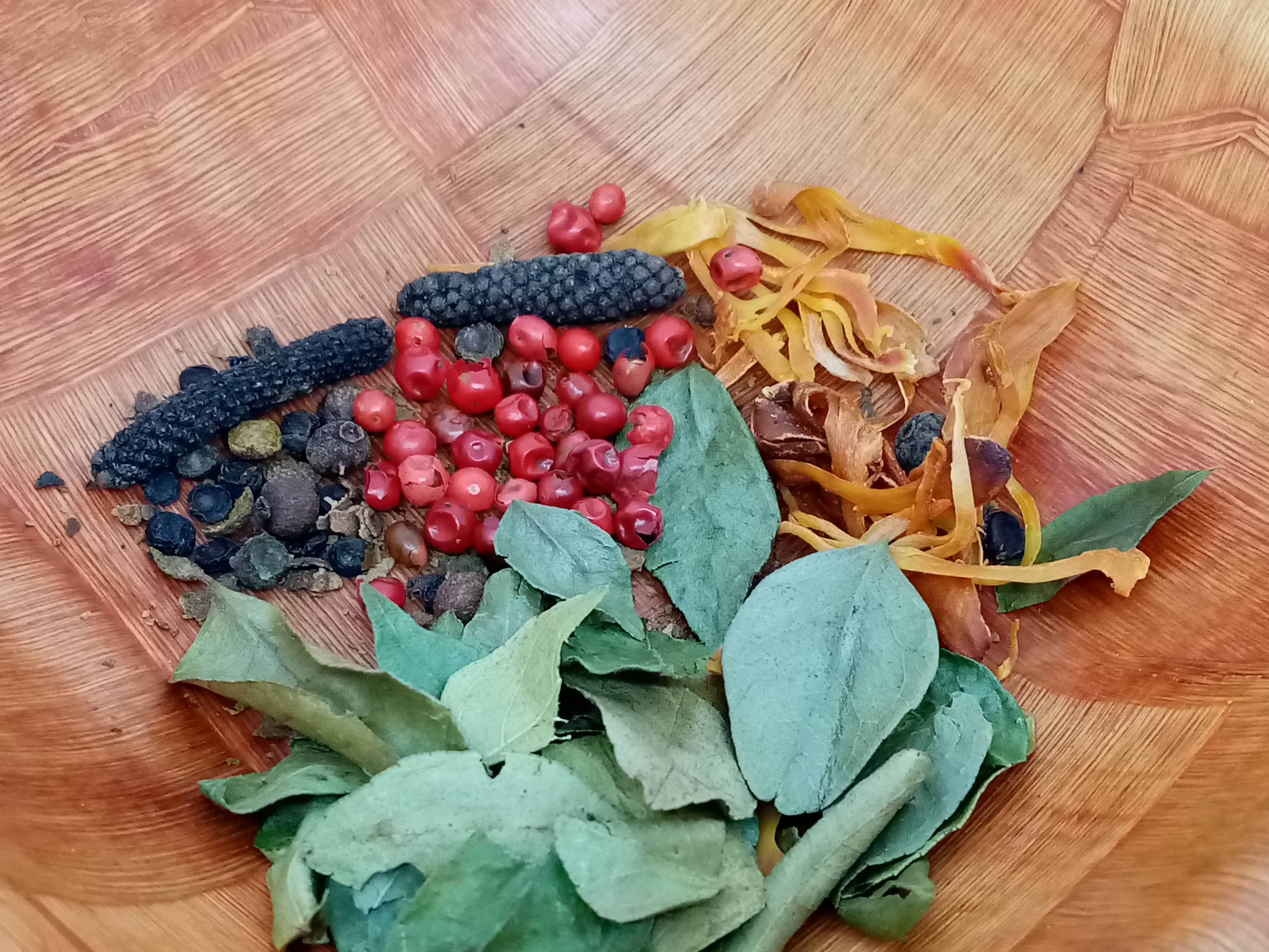 species in a bowl: bay leaves, red pepper corns, nutmeg flowers, long black pepper