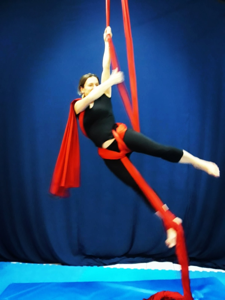 a lady in black doing sport: holding a red band in the air, blue curtain back ground