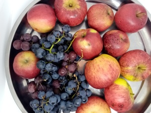 dark grapes and apples on a metal round tray, top view
