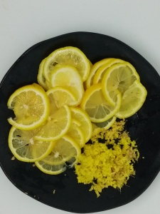 cut lemon slices and grate ginger on a black plate