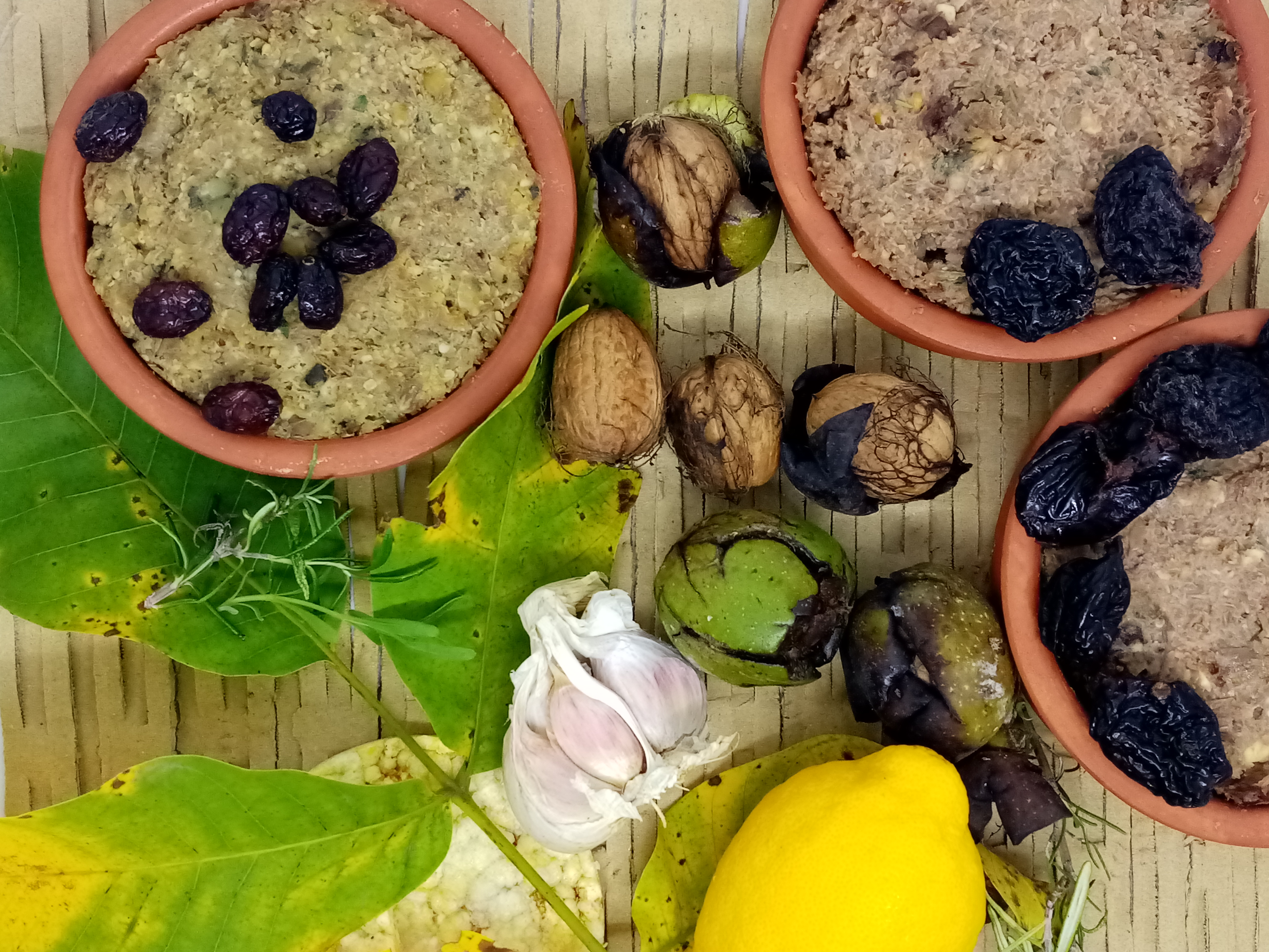 apetizers in clay bowls on a table decorated with tree leaves, whole walnuts, lemon and garlic cloves