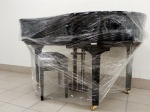 black grand piano wrapped in plastic close to a white wall
