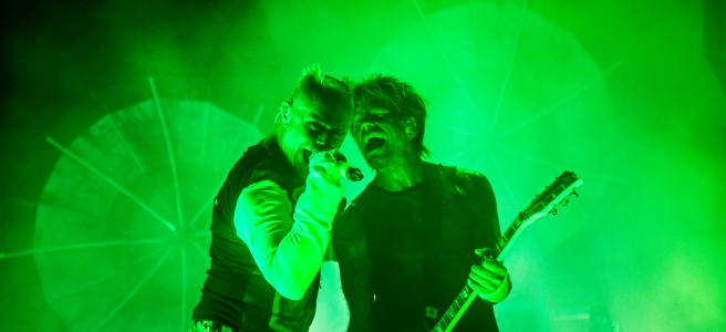 one man with microphone and one man with a guitar singing together. green background with light effects on a scene