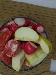 cut apples, grapefruits and radishes on a round metal plate