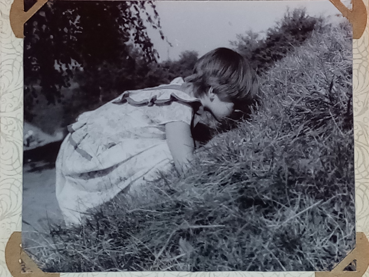 a girl with short hair looking to grass, grey photo