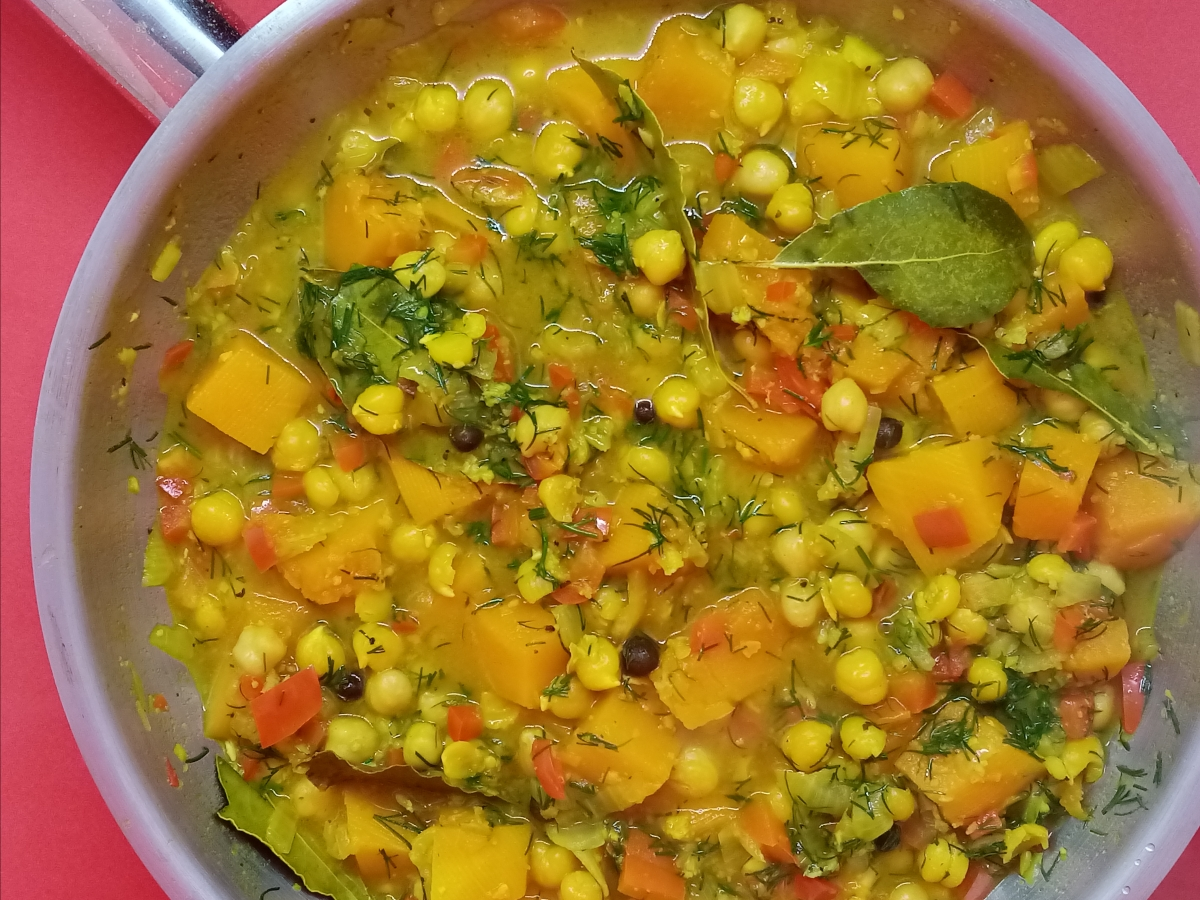 yellow color stew with spices in a pan, top view, red background